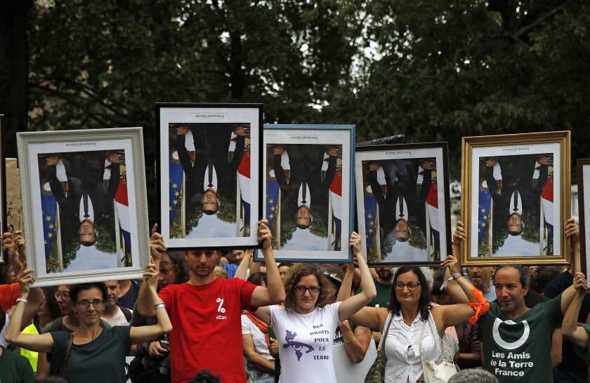 FILE - In this Aug.25, 2019 file photo, demonstrators hold up upside down portraits of French President Emmanuel Macron during a protest in Bayonne, France. One by one, environmental activists around France have been taking portraits of President Emmanuel Macron down from scattered town halls this year. The portrait-removers, have been facing trials around the country, with some fined, others released. An appeals court in Lyon is reconsidering the first conviction handed down over portrait removal Tuesday. (AP Photo/Emilio Morenatti, File)