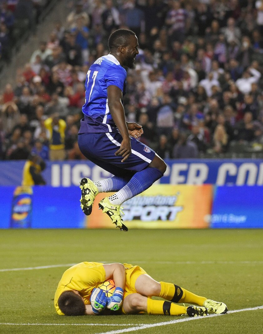 United States' Jozy Altidore, top, jumps over Canada goalkeeper Maxime Crepeau after Crepeau made a save during the first half of an exhibition soccer match Friday, Feb. 5, 2016, in Carson, Calif. (AP Photo/Mark J. Terrill)