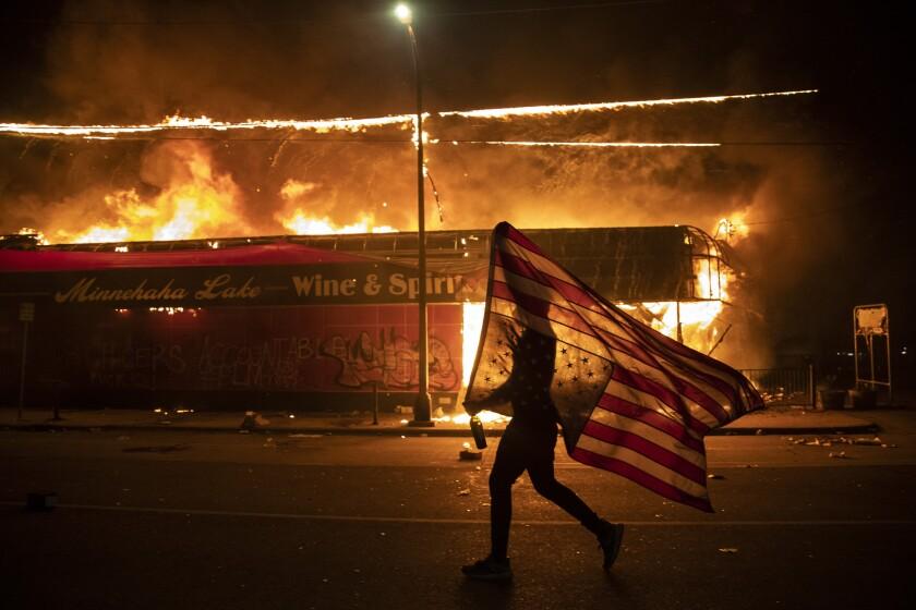 Un manifestante lleva una bandera estadounidense invertida, señal de estar en peligro