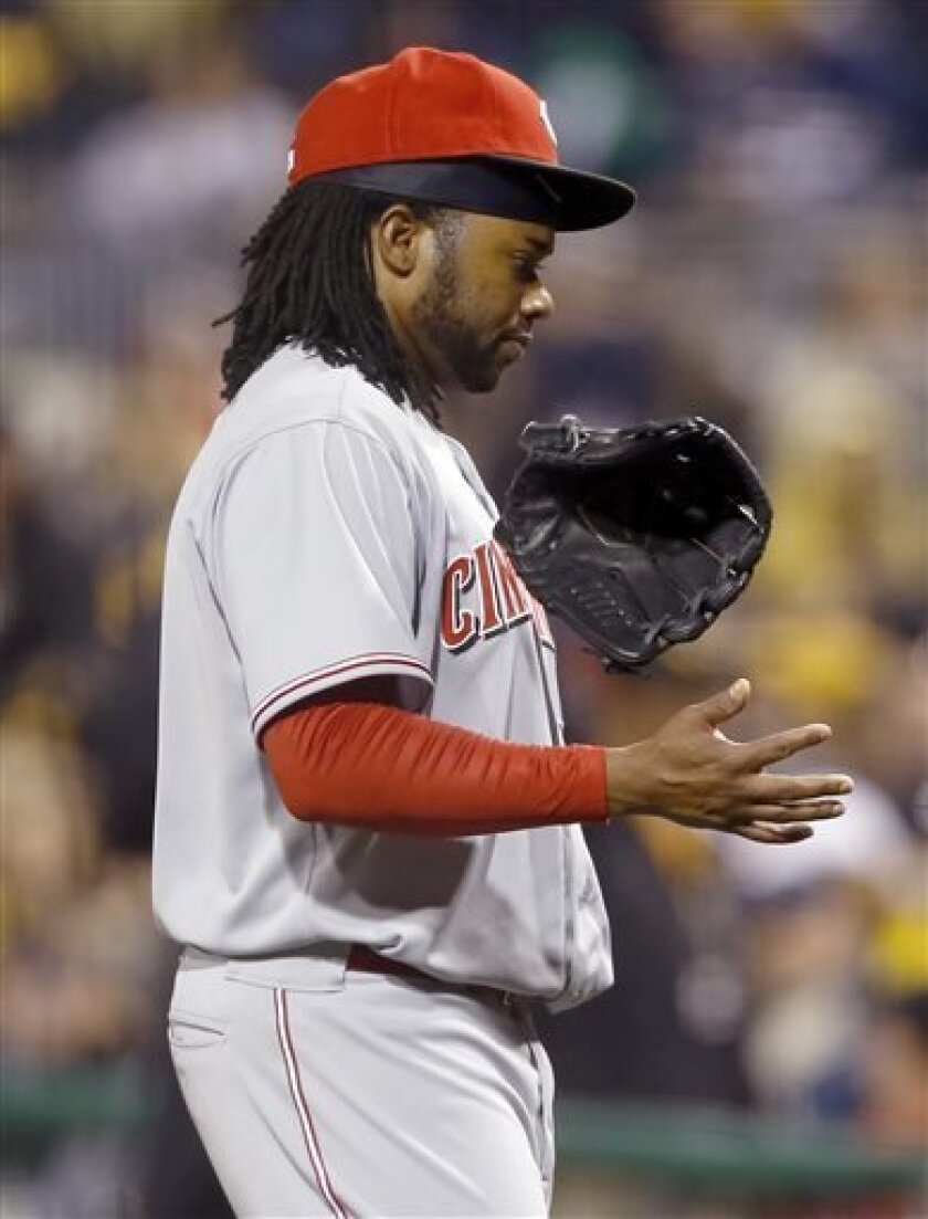 Cincinnati Reds starting pitcher Johnny Cueto tosses his glove as he leaves the game after apparently injuring his arm throwing to Pittsburgh Pirates' Pedro Alvarez in the fifth inning of the baseball game on Saturday, April 13, 2013, in Pittsburgh. (AP Photo/Keith Srakocic)