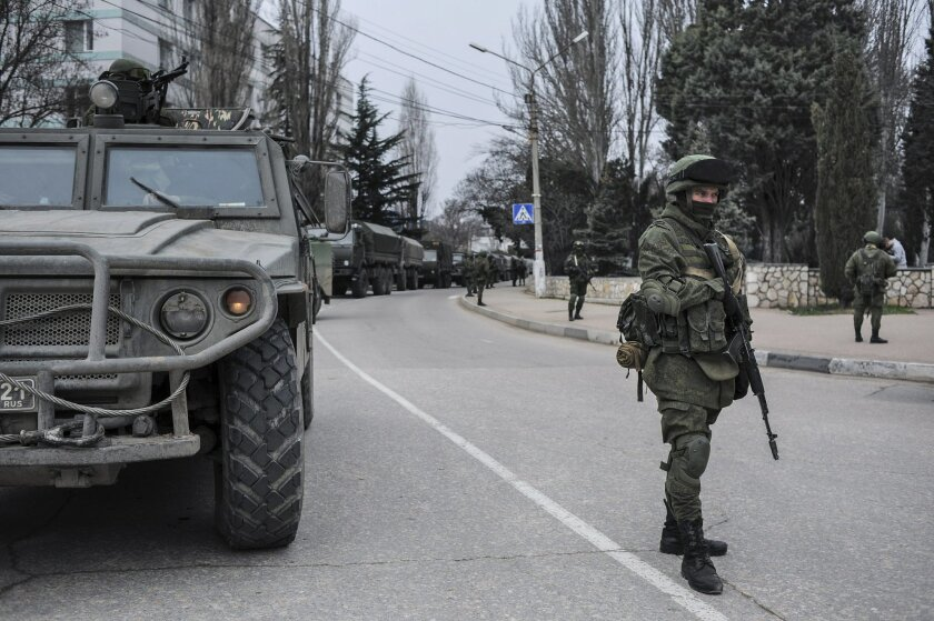 Troops in unmarked uniforms stand guard in Balaklava on the outskirts of Sevastopol, Ukraine, Saturday, March 1, 2014. An emblem on one of the vehicles and their number plates identify them as belonging to the Russian military. Ukrainian officials have accused Russia of sending new troops into Crim