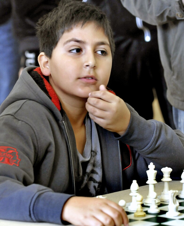 Eleven-year-old Hovanes Salvaryan of Hollywood contemplates his move during a practice match at L.A. Holiday Scholastic Chess Championships held at the Maple Park Community Center in Glendale on Sunday, Dec. 8, 2013.