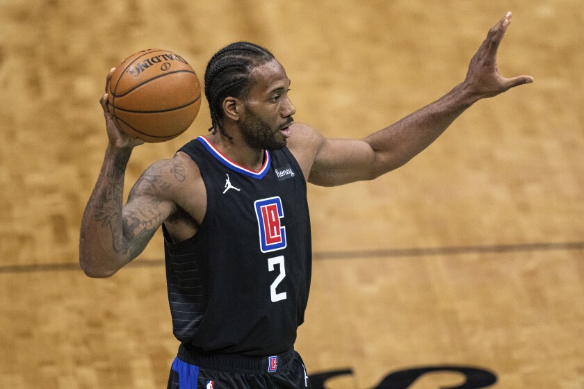 FILE - In this May 31, 2021, file photo, Los Angeles Clippers forward Kawhi Leonard looks to pass the ball during the team's NBA basketball game against the Charlotte Hornets in Charlotte, N.C. Leonard is staying in Los Angeles after the Clippers re-signed him. Leonard sustained a partially torn right ACL during the recent playoffs, and missed the Clippers' run to their first Western Conference finals appearance. He had surgery on his knee a month ago. (AP Photo/Jacob Kupferman, File)