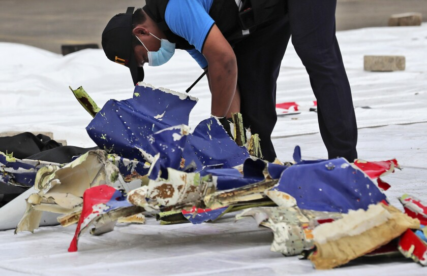 An investigator inspects parts of Sriwijaya Air Flight 182 that crashed.