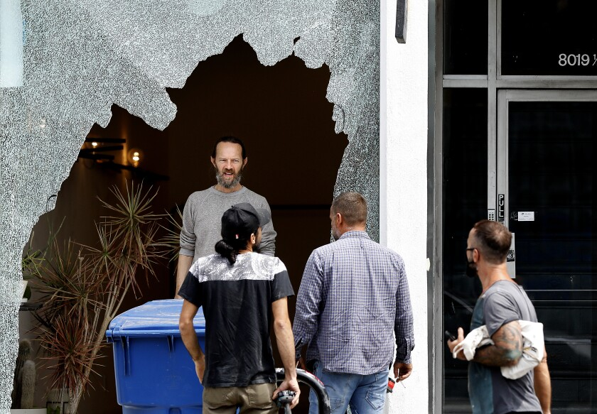 People gather in front of a shattered storefront window