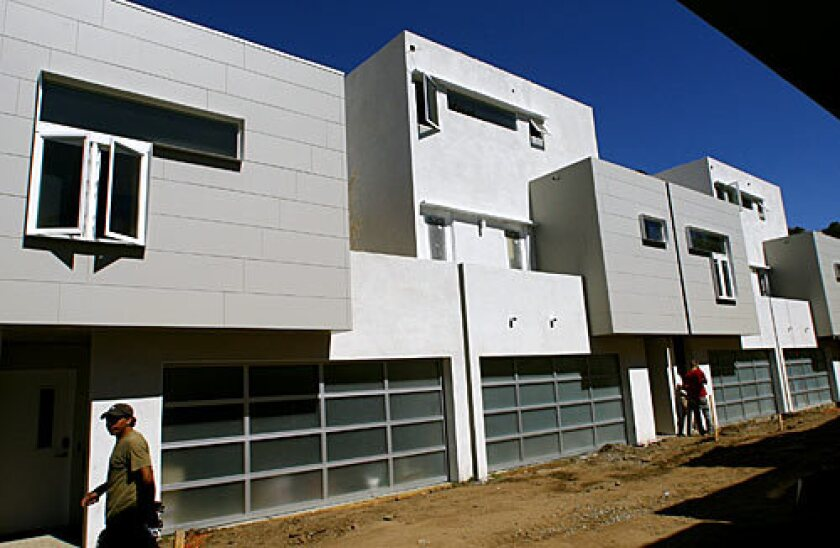 """By Chris Iovenko, Special to The Times From a distance, the 15 homes being built on half an acre in the Eagle Rock neighborhood of L.A. look like your typical small-scale condo development. You could call them townhomes, but look more closely and there's one key difference: a tiny gap of air between each unit. """"The buildings don't share a common wall,"""" says architect Kevin Wronske, who with brother Hardy also is the developer of the project, called Rock Row. """"There is five inches of space between each of them that is totally open."""" The gaps allow each building to move independently of the others in an earthquake. Perhaps most important, the space serves as sound insulation, lessening how much noise transfers from one unit to the next. Tag along as writer Chris Iovenko peeks inside... Back to L.A. at Home"""