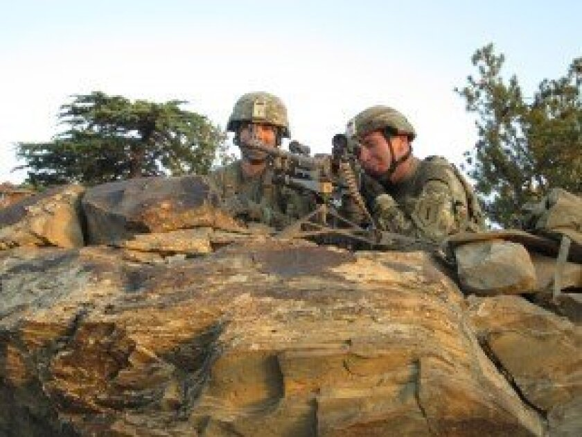 PFC Popescu and Gunner Vaughan watching a village