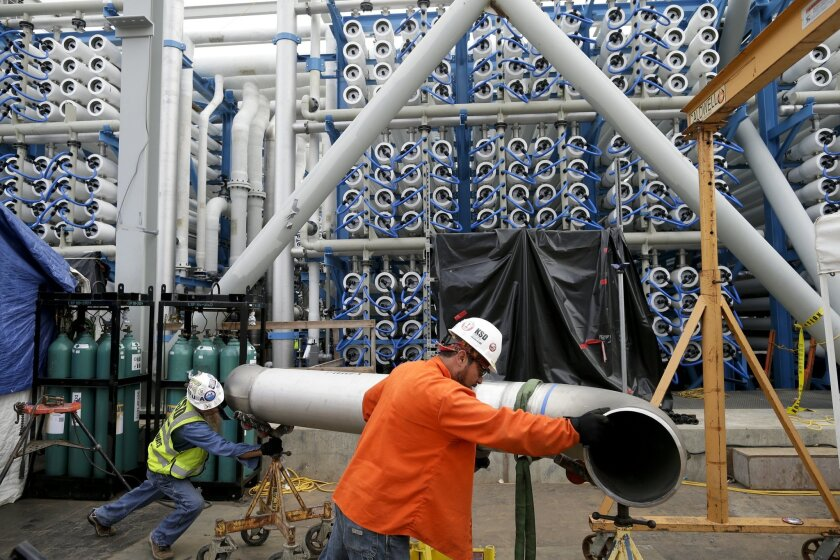In this March 11, 2015 picture, workers move a pipe in front of the 2000 pressure vessels that will be used to convert seawater into fresh water through reverse osmosis in the western hemisphere's largest desalination plant Wednesday, March 11, 2015, in Carlsbad, Calif. Despite the San Diego region