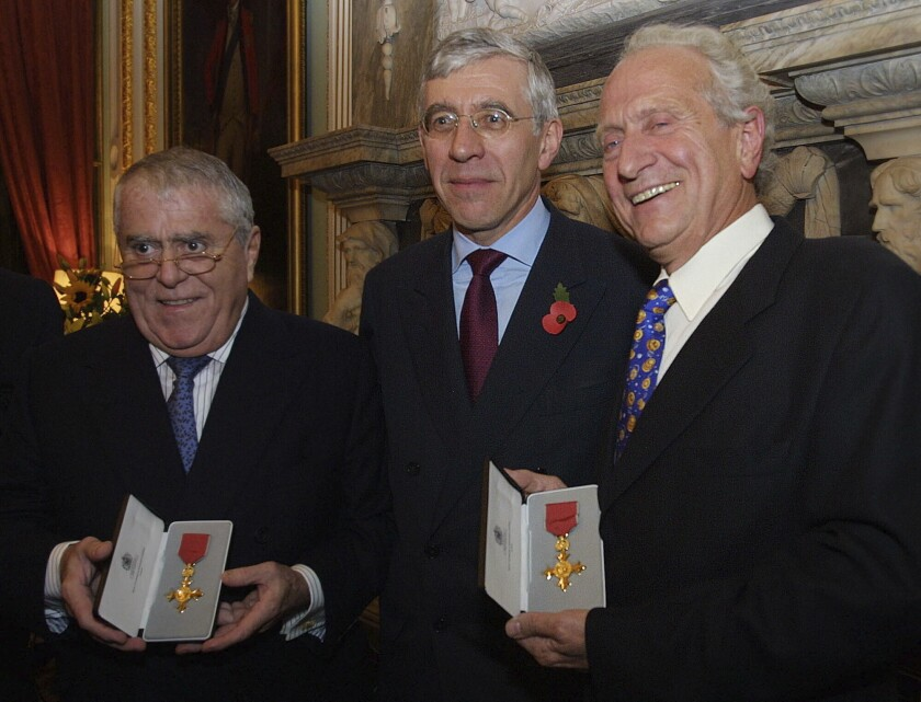 FILE - In this Thursday, Oct. 31, 2002 file photo, Albert, left, and Michel Roux, right, receive their Order of the British Empire honorary awards from the British Foreign Secretary Jack Straw during a ceremony at the Foreign Office in London. Michel Roux, the French-born chef who had a profound influence on Britain's fine dining habits, has died on Thursday, March 12, 2020. He was 78. (AP Photo/Alastair Grant, file)