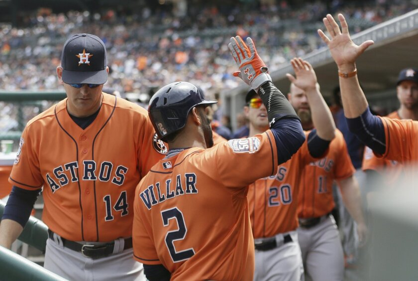 Houston Astros' Jonathan Villar is congratulated after scoring during the seventh inning of a baseball game against the Detroit Tigers, Thursday, May 21, 2015, in Detroit. (AP Photo/Carlos Osorio)