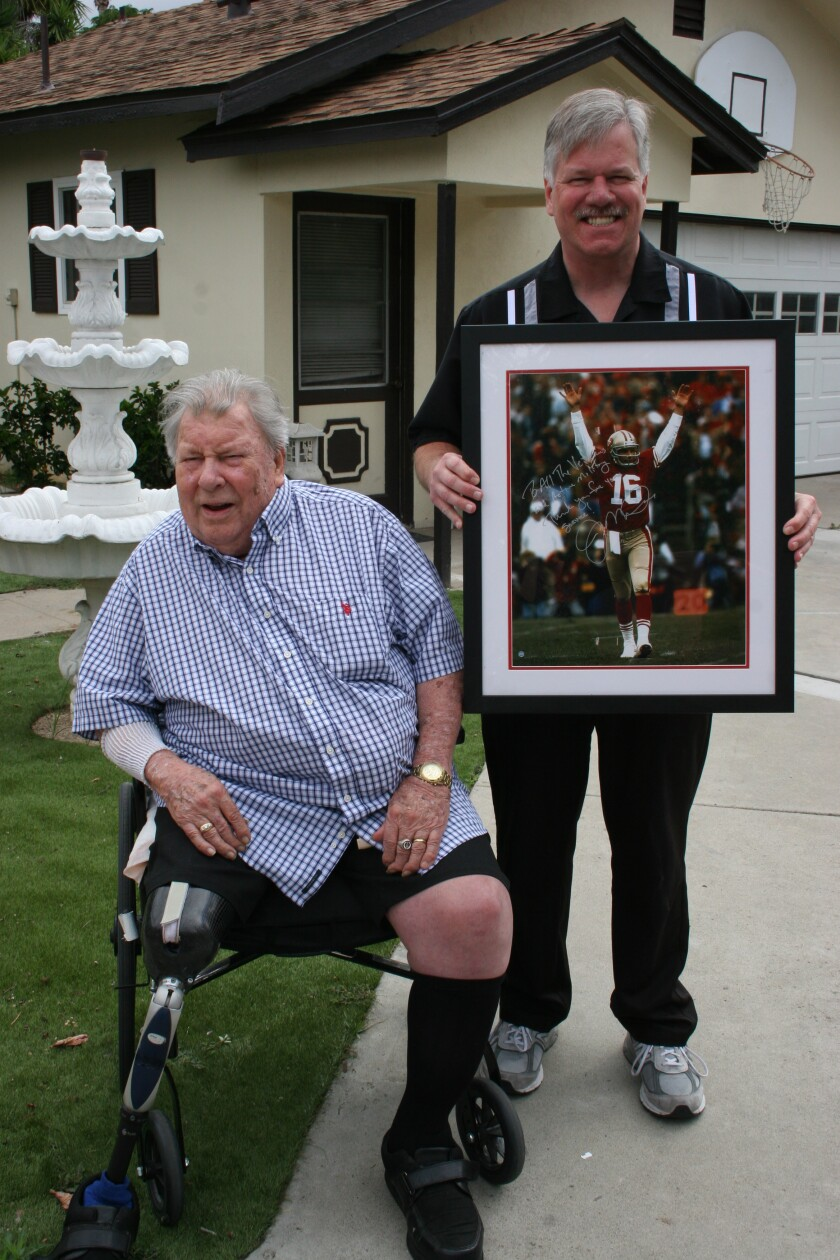 """Marine Corps veteran Robert Olsen plans to donate a photo of Joe Montana he received this summer. Montana wrote on the photo, """"To All of Our Veterans and Active Military Thank You for Your Service."""" Olsen plans to donate the picture to Camp Pendleton. Olsen participated in the Inchon Landing in South Korea and was wounded and lost his right leg while serving in the Korean War. Olsen is pictured with his son Jeffrey Olsen, right, known locally as the 'Toyman,' because of his efforts to donate toys to needy area children. Jeffrey has been recognized with a number of awards for his humanitarian work, which includes clothing and food drives and other community work over several decades."""