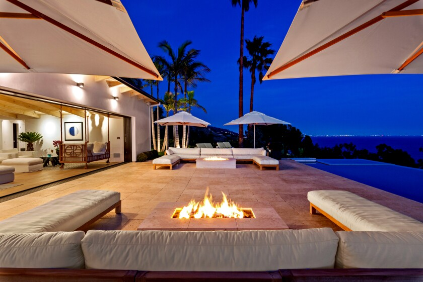 The contemporary-style home, developed by former Hollywood duo Janus Cercone and Michael Manheim, sits on a lush, one-acre lot in Malibu with 270-degree ocean views. Tropical landscaping creates a backdrop for an adult treehouse, hidden pathways and a hammock installed between two trees. There's also a 12-person spa and an infinity-edge pool that can be controlled by a smartphone. Listed for $11.45 million, the single-story house was redesigned so that all but one room takes in a view of the ocean, while skylights were added to bathe the interior in natural light. Among features is a custom Moroccan amethyst geode sink in the powder room. The unique sink fixture is fed by a ceiling faucet.