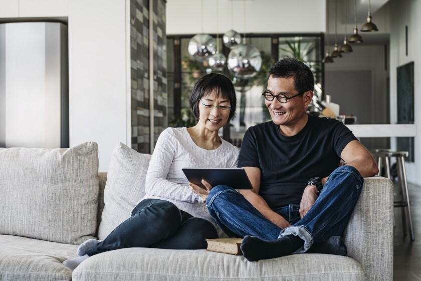 Chinese couple on sofa watching movie online