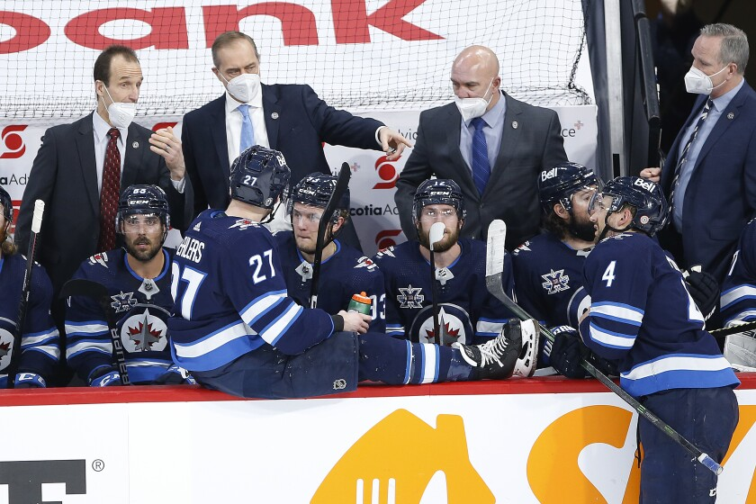 Winnipeg Jets coach Paul Maurice talks to players during the third period of Game 2 of an NHL hockey Stanley Cup second-round playoff series against the Montreal Canadiens on Friday, June 4, 2021, in Winnipeg, Manitoba. (John Woods/The Canadian Press via AP)