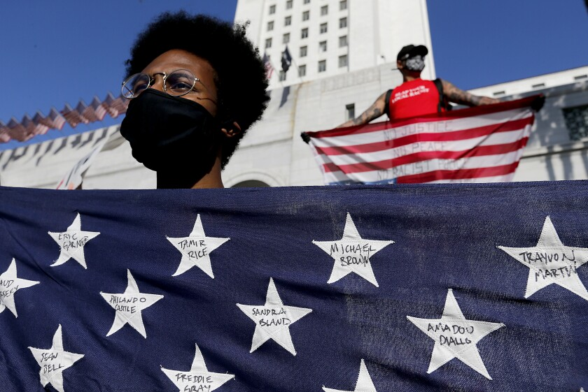 A protester holds a flag with the names of victims of violence during a demonstration June 4 in downtown Los Angeles.