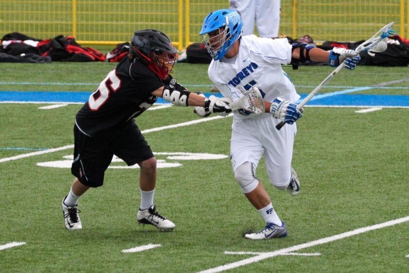 La Jolla Country Day junior David Brewster (5) makes a move on La Jolla High freshman Cavan Walsh (36) on Saturday. Brewster and Walsh each scored goals in the game as the visiting Vikings edged the Torreys 8-6.
