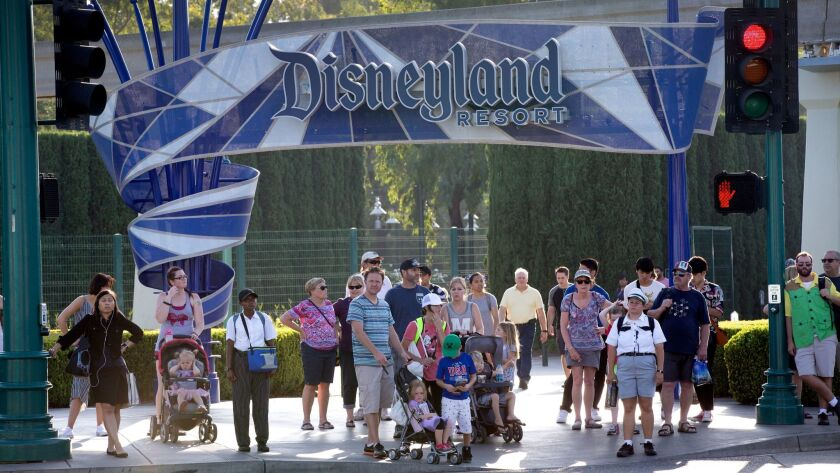 Disneyland patrons exit the park under the Disneyland sign at a shuttle area in Anaheim in 2017. A proposed city ordinance would require the resort to raise hourly wages for its workers.