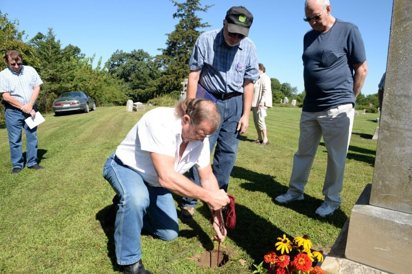 In this photo taken Thursday, Aug. 20, 2015, Mark Wagler buries the ashes of Daisy Walker, a distant relative, at the North Walker Cemetery in Burlington, Iowa. Wegner died in the confines of the Oregon State Hospital in 1957, and her ashes stayed there until the remains were discovered and sent to the Wagler family earlier this year. (Jeff Brown/The Hawk Eye via AP) MANDATORY CREDIT