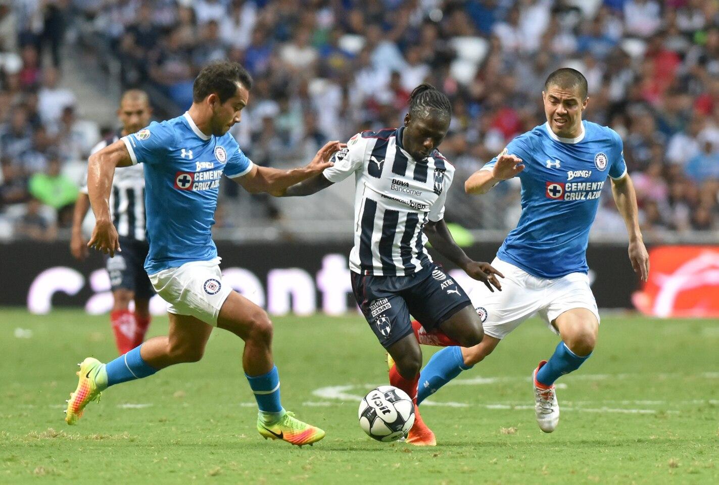 Yimmi Chará (c) de Rayados de Monterrey disputa el balón con Adrian Aldrete (i) y Franisco Silva (d) de Cruz Azul, en un partido correspondiente a la jornada 3 del Torneo Apertura 2016 en el estadio BBVA de la ciudad de Monterrey.