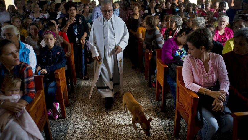 Father Cirilo Castro walks down the aisle of the newly inaugurated Parish of the Sacred Heart of Jesus in Sandino, Cuba, on Saturday.