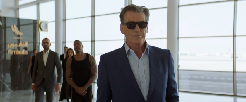 """A man in sunglasses walks through an airport followed by two tough guys in the movie """"The Misfits."""""""