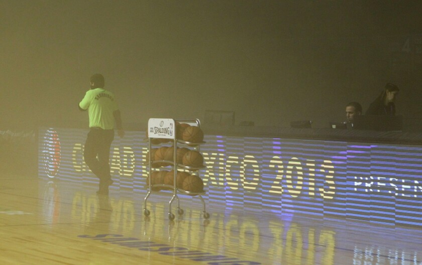 Smoke engulfs a Mexico City arena prior to the scheduled tipoff between the San Antonio Spurs and Minnesota Timberwolves on Wednesday. The arena was evacuated and the game was postponed.