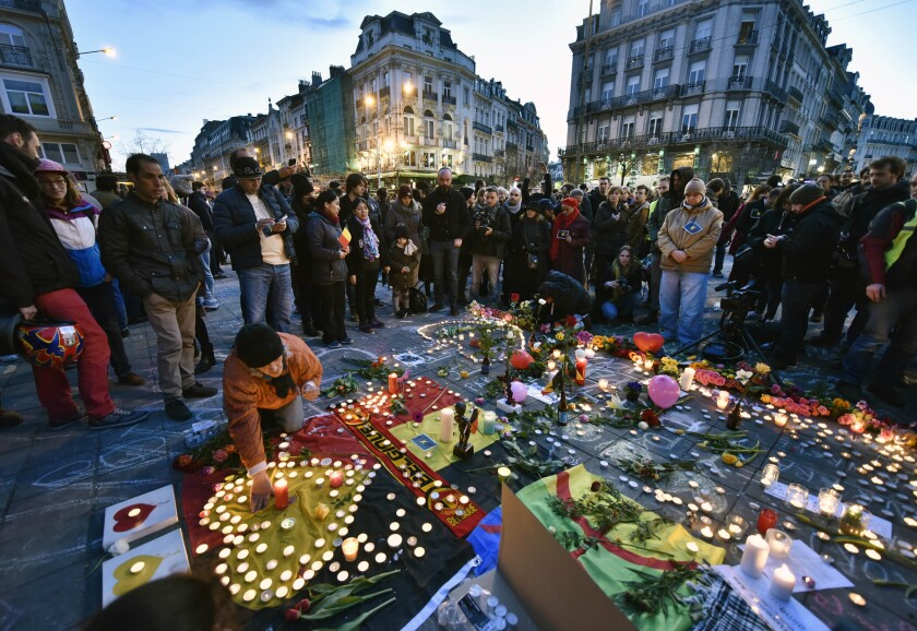 People bring flowers and candles to mourn at the Place de la Bourse in the center of Brussels after bombs exploded at the city's airport and one of the metro stations Tuesday. More than 34 people died in the blasts.