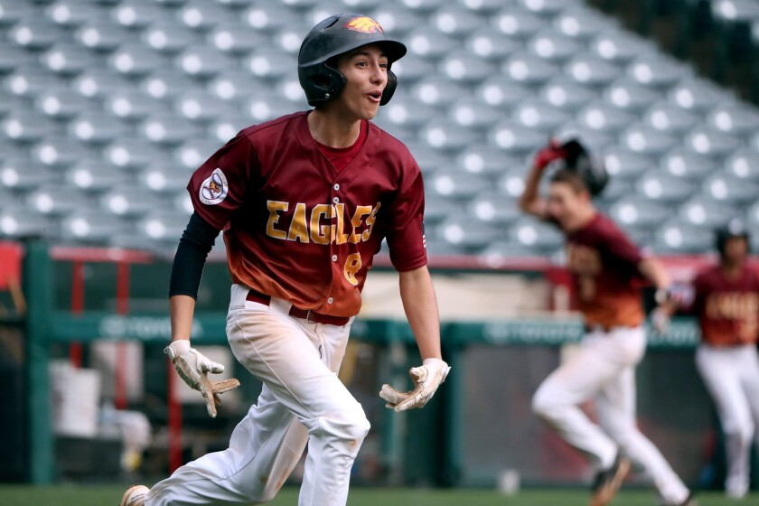 Estancia High School player #8 Nick Perales runs to first base after driving in the game-winning run