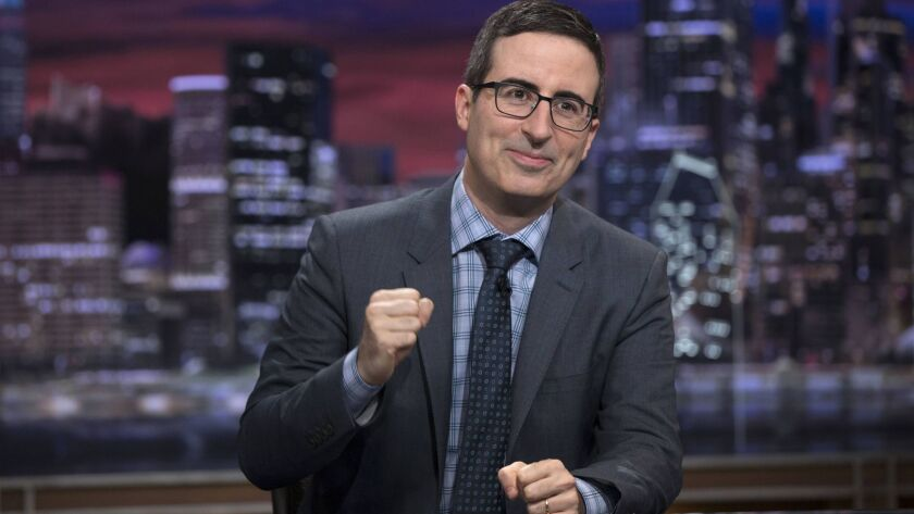 """This image released by HBO shows John Oliver on the set of """"Last Week Tonight with John Oliver."""" Wit"""