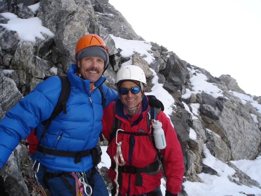 Two men in climbing gear stand on a rocky, icy mountain