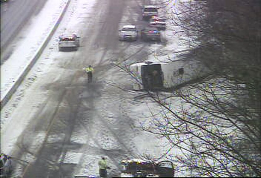 In this image from a Connecticut Department of Transportation traffic camera, a bus lies on the shoulder of northbound Interstate 95 Monday, Feb. 8, 2016, in Madison, Conn. The charter bus on its way from New York city to the Mohegan Sun casino crashed during a snowstorm, leaving at least 30 people