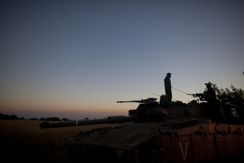 Israeli soldiers with a tank on the border with Syria on Sunday. An Israeli teen was killed and three adults were wounded in an attack near the border. Later, Israeli airstrikes hit nine military targets in Syria.
