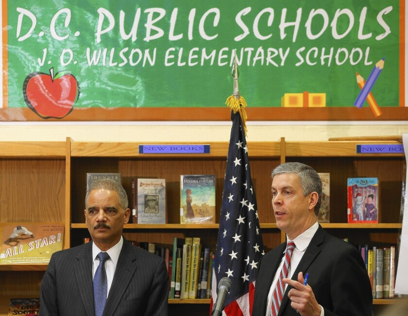 Atty. Gen. Eric H. Holder Jr., left, and Education Secretary Arne Duncan discuss results of a new civil rights study on access to education and unfair disciplinary practices in U.S. public schools during a visit to J.O. Wilson Elementry School in Washington.