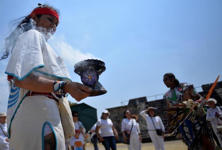 Turistas y visitantes observan a danzantes durante un rito de la llegada del equinoccio de primavera hoy, miércoles 21 de marzo de 2018, en el municipio de Xochitepec, Morelos (México). Paseantes acuden a la zona arqueológica de Xochitepec para recibir energía por la llegada de la primavera. EFE