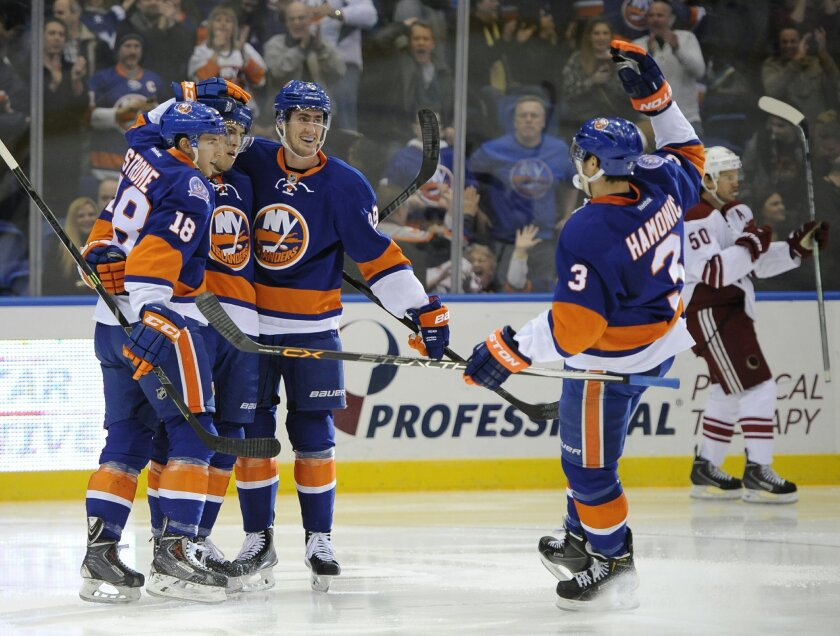 New York Islanders center Ryan Strome (18), center Anders Lee (27), center Brock Nelson (29) and defenseman Travis Hamonic celebrate Lee's goal as Arizona Coyotes center Antoine Vermette (50) skates away in the second period of an NHL hockey game Tuesday, Feb. 24, 2015, in Uniondale, N.Y. (AP Photo/Kathy Kmonicek)