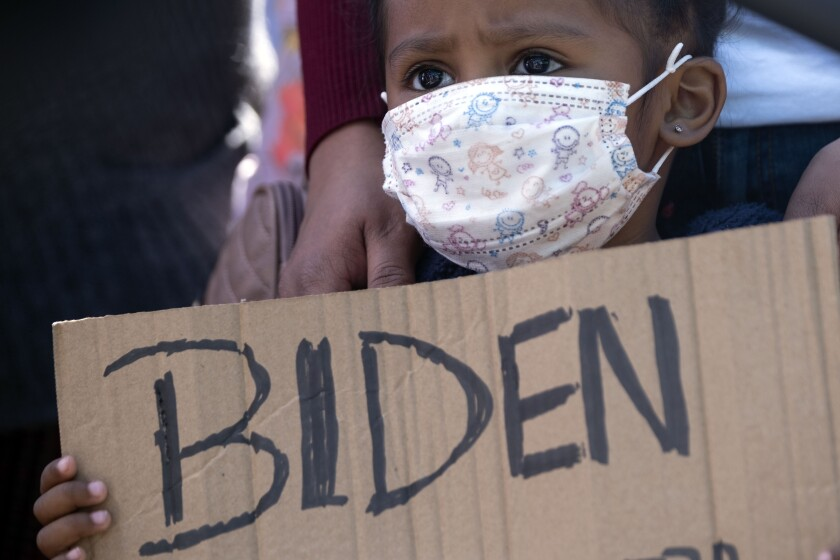 Honduran girl holding Biden sign in Tijuana.