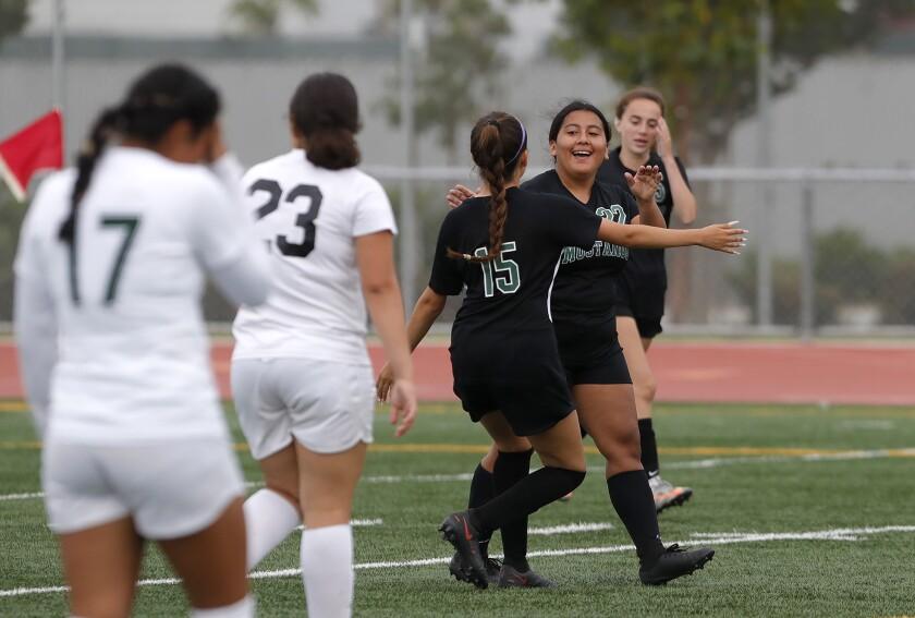 Costa Mesa's Brianna Calderon (15) runs up to congratulate Belen Ramirez after a goal against Saddleback on Thursday.