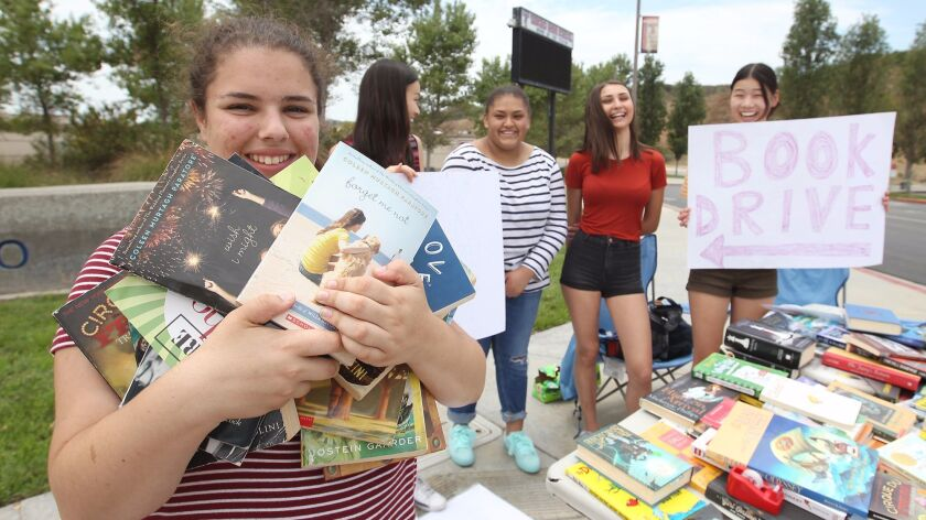 Sara Kurd-Misto, left, co-founded FirstBook Tesoro, a book club which helps raise money and gather books for those in need. She gets support from Sydney Kim, Breeana Warren, Oksana Aldendeshe and Taylor Kim, from left, during the recent drive.