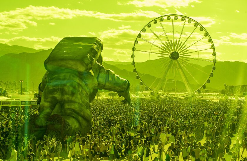As seen through green plexiglass, a massive astronaut figure and a Ferris wheel tower over the crowd on day one of the Coachella Valley Music and Arts Festival.