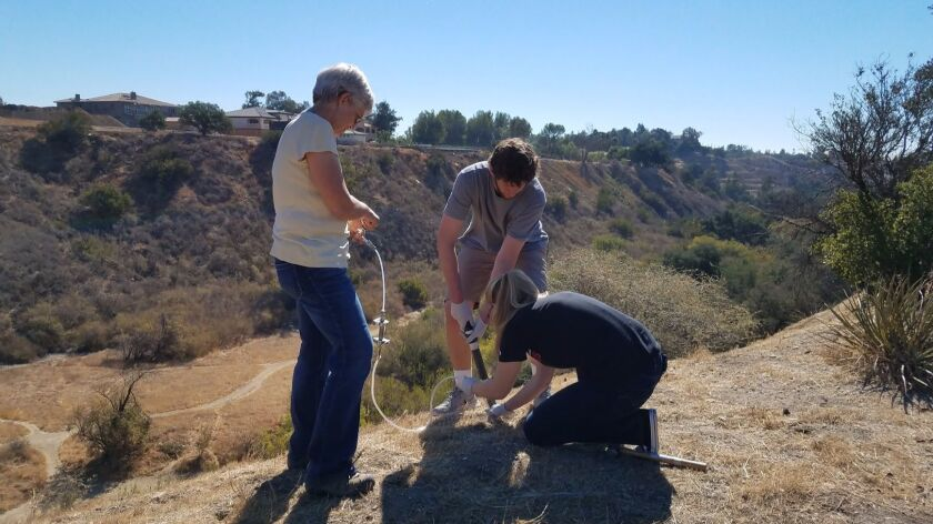 Cal State Channel Islands student Alex Safian, center, removes a soil sample from a site 4 kilometers from the leaking well, while fellow CSUCI student Allison Teunis, right, and Caltech scientist Sally Newman quickly place tubing into the cored hole to sample trace gas.