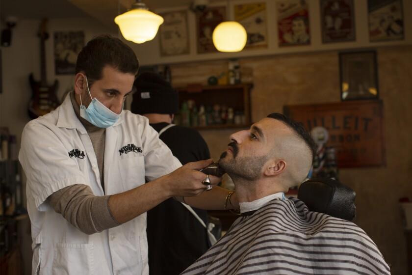 Un cliente es atendido en la barbería Nashville Barber Shop, en Jerusalén, el 23 de febrero de 2021.