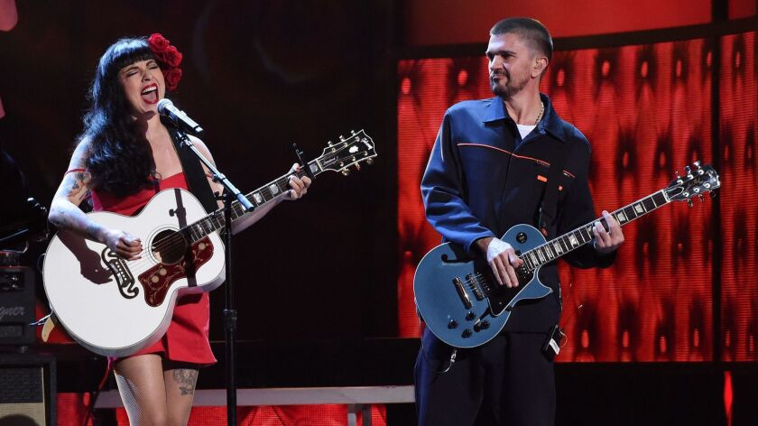 Chilean singer-songwriter Mon Laferte with Colombian pop star Juanes, accompanying her on guitar.