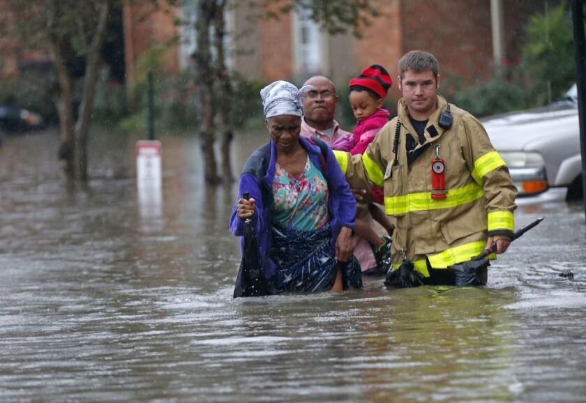 Un integrante del Departamento de Bomberos de St. George apoya a residentes mientras caminan en las aguas de una inundación tras intensas lluvias, en los apartamentos Chateau Wein en Baton Rouge, Louisiana. (AP Foto/Gerald Herbert)