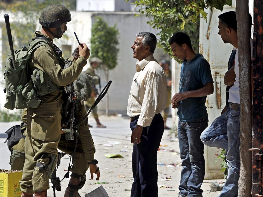 Israeli soldiers question Palestinians during a search operation Wednesday in Tapuah, west of Hebron, in the West Bank.