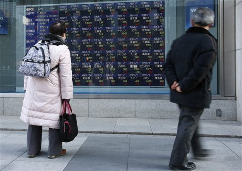 People watch the electronic stock board of a securities firm in Tokyo, Wednesday, Feb. 20, 2013. Asian stock markets picked up stream Wednesday, driven higher by reports that another big corporate takeover might be in the works in the U.S. (AP Photo/Shizuo Kambayashi)