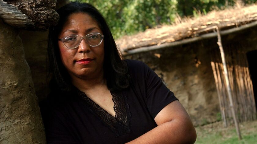 Marilyn Vann, whose family is black with Cherokee blood, poses in a re-creation of a Cherokee village at the Cherokee National Museum in Tahlequah, Okla. The Cherokee Nation is denying her citizenship.