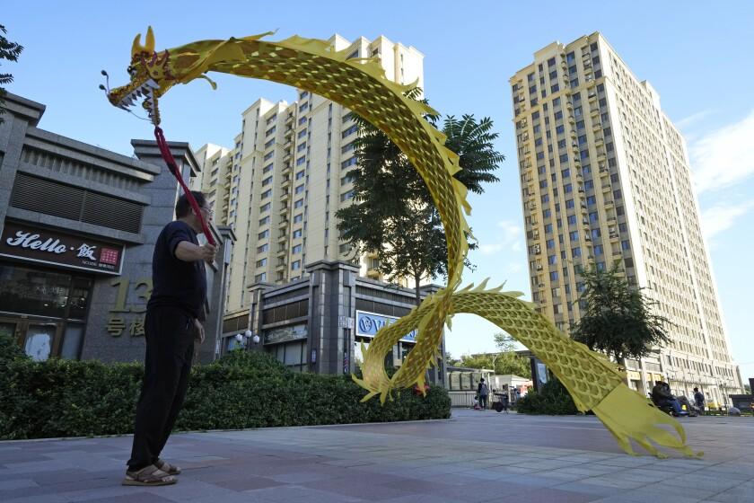 Una persona hace ondear un dragón de tela ante el complejo residencial Evergrande Yujing Bay en Beijing, China, el martes 21 de septiembre de 2021. Inversionistas de todo el mundo seguían las noticias con nerviosismo mientras una de las mayores promotoras de bienes raíces de China trataba de evitar la suspensión de pagos en deudas multimillonarias, lo que podría tener amplios efectos en el sistema financiero. (AP Foto/Ng Han Guan)