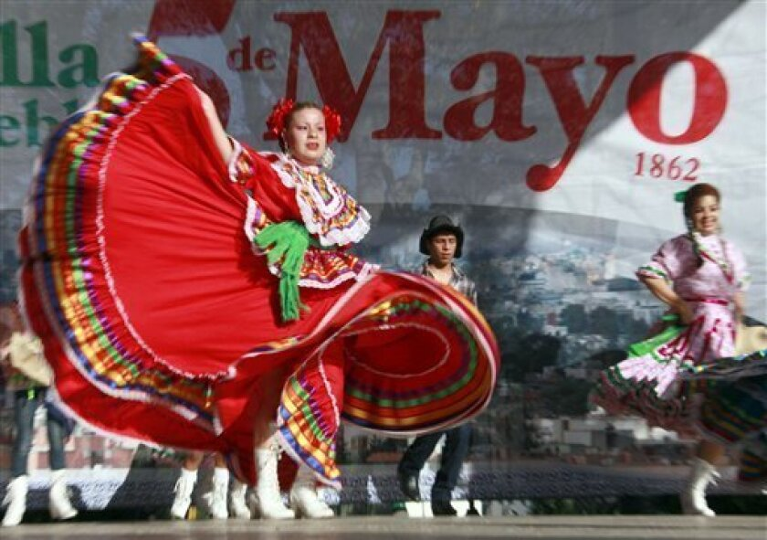 FILE - In this May 5, 2011 file photo, Marylin Castillo dances in honor of the Cinco de Mayo celebration in Los Angeles.  Cinco de Mayo has become in the U.S.: a celebration of all things Mexican, from mariachi music to sombreros, marked by schools, politicians and companies selling everything from