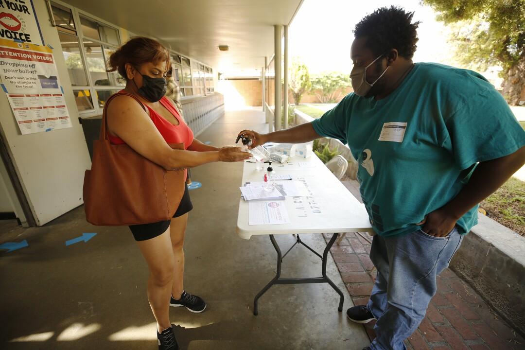 Wahlhelfer Marcus Offutt (rechts) verteilt Händedesinfektionsmittel an Dolly Shukla (links), die sich den Wählern anschließt, die ihre Stimmzettel abgeben