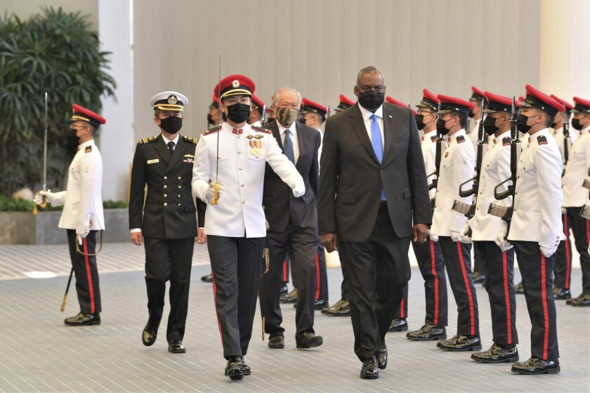 In this photo provided by the Singapore Ministry of Defense, U.S. Defense Secretary Lloyd J. Austin along with Singapore Defense Minister Ng Eng Hen, back, review an honor guard at the Ministry of Defense Tuesday, July 27, 2021 in Singapore. Austin decried the actions of Myanmar's military rulers as unacceptable on Tuesday, while urging a regional bloc to keep demanding an end to violence. Austin also applauded the Association of Southeast Asian nations for its efforts on the issue, which included forging a consensus with Myanmar's military leader in April. (Singapore Ministry of Defense via AP)